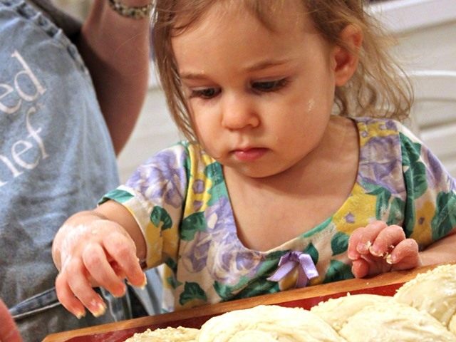 Toddler sprinkling seeds on her challah dough