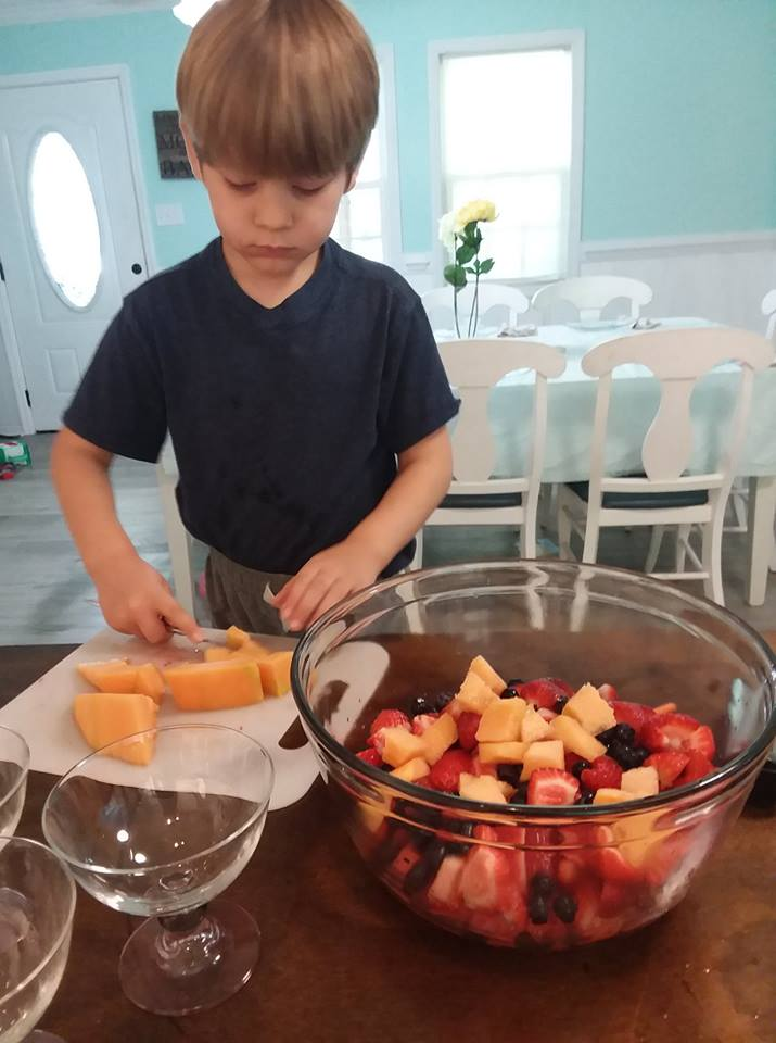 preschooler helping cut fruit